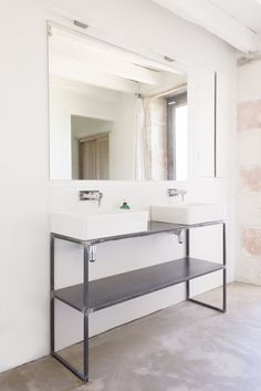 Bathroom sinks on black metal stand, alongside a large mirror on the wall. Project 'Sereine' by Septembre. Photo by Linus Ricard.