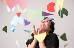Woman smiling at falling pieces of colorful paper