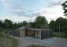 Timber holiday home huddles behind dunes on Dutch island