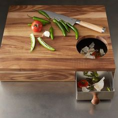 Storage Cutting- This cutting board has a hole in one corner that allows you to sweep peelings and trimmings into a hidden metal drawer th