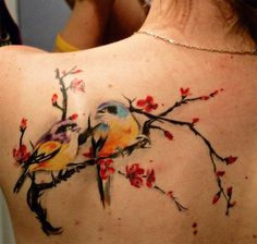 A very pretty looking tattoo of two birds perched on a branch with red flowers. The style which the birds are drawn is also very attractive
