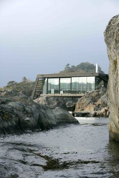 Balancing on irregular, rough-hewn rocks along the Norwegian coast, this renovated summer cabin near a town called Larvik in Vestfold County intelligently navigates a challenging terrain to take full advantage of dramatic views. Located just about 16 feet from the sea, Lille Arøya—a 807-square-foot summer cabin—perches on a small, rugged island. Oslo-based practice Lund Hagem Architects took on the challenge, drilling solid galvanized steel columns straight into the rock to provide stable support for the house on the uneven ground. They built a new structure that consists of two volumes:a lower post-and-beam volume where the bedrooms and bathrooms are located, and a taller volume with a large, cantilevered roof with wind-bracing gables that serves as shelter for the living, kitchen, and dining areas. Glulam beams are used inside and out, and both interior and exterior walls are clad in rough sawn ore pine. Together with the raw steel columns and white concrete fireplace, the wood defines the color and mood of the interiors. The uniform aesthetic of the cabin's interior and exterior dissolves the threshold between indoor and outdoor spaces—and further connects the structure with its stunning, coastal landscape. Tagged: Exterior, House, Cabin Building Type, Flat RoofLine, and Green Roof Material. Photo 7 of 11 in Dwell's Top 10 Cabins of 2017 from A Norwegian Summer Cabin Embraces the Rocky Terrain