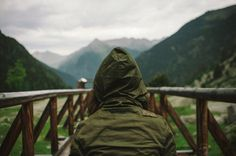 a young woman with her back to us wearing a green hooded jacket standing on a bridge with mountains spread out in front of her #photography