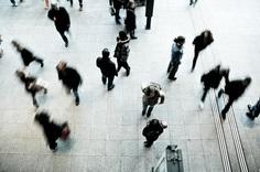 An overhead shot of people walking across a railway station