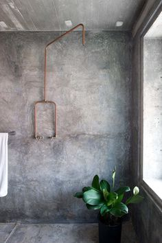 #Concrete #bathroom with exposed copper #pipeshower. Home of #WenHsiaAndBCAng. Photograph by #MarjonHoogervorst.