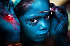 Divine Makeover :: Photo and caption by Mahesh Balasubramanian / National Geographic Traveler Photo Contest #girl #india #child #culture #paint #photography #blue #face #beauty