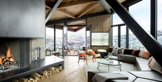 An Angular Mountain Retreat in Colorado Captures Breathtaking Views. Living Room, Sectional, Coffee Tables, Chair, Standard Layout Fireplace, Rug Floor, Recessed Lighting, Ottomans, Wood Burning Fireplace, and Medium Hardwood Floor.