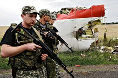 Armed Russian-backed militants pass next to the wreckage of a MH17 flight which crashed during flight over Donetsk