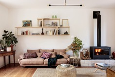"""Fielders replaced an inefficient 1960s fireplace with a clean-burning Invicta stove: """"when that thing is cranking, it warms up the entire ground floor."""" The sofa is is the Canapé Lenakine from AM.PM, """"the French equivalent of Habitat."""" The ceiling light is Zangra's Porcelain and Metal Lamp."""
