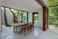 Dining room opens to courtyard. House on a Stream by Architecture BRIO. © Sebastian Zachariah. #diningroom #asian