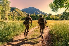 Two Combat Soldiers Take Off Running Across Open Field