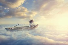 Caucasian girl sitting in rowboat in clouds