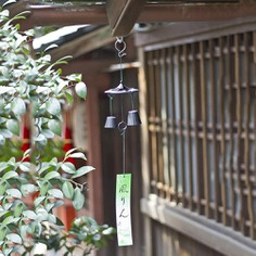 Also known as 'nambu furin', this exquisite wind bell is crafted from cast iron and is traditionally hung outdoors from the eaves of houses or near windows in Japan. It has a strip of paper that elegantly hangs from a ringer, working as a wind catcher. When the wind blows, it causes the ringer to strike the furin's bells and produce a soft and soothing sound. Made in Japan.
