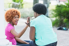 African American mother and adult daughter, high five