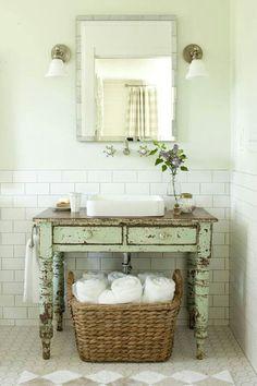 Adding a vintage-inspired vanity gives this bathroom a rustic vibe. Love the big basket of towels #vintage #bathroom