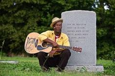 "Photo of Mississippi blues musician, guitar player Pat Thomas at his Dad's grave , photographed in Leland, MS in the delta along the Blues Highway, Highway 61 near The Crossroads. Photographed for Moonshine & Mojo Hands. Pat Thomas is the Son of James ""Son"" Thomas, the legendary bluesman. Environmental portrait. We are an industrial photographer, on location photographer & location commercial photographer. Shallow depth of field and selective focus."