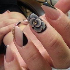 A very seductive looking nail art design in striking black, gray and gold details, with gold dust and a huge gray flower detail adorned with