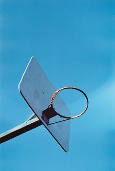 A baseball hoop without the net against a blue sky