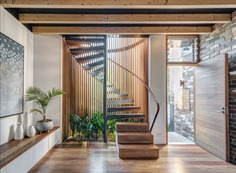 A cylindrical glass staircase with Western red cedar and painted steel mullions dominates the front of the house. The stair treads, along with the floor, are made of recycled spotted gum. Cedar spiral staircase.