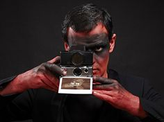 Man making a picture with vintage polaroid SX70 #red #photo #black #polaroid #paint #photography #raar #face
