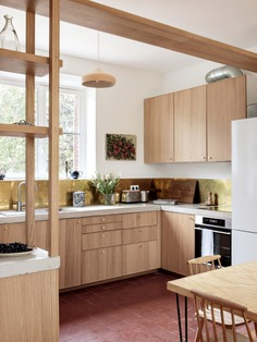 Oak display shelves divide the dining area from the kitchen. The oak-fronted Ikea cabinets are topped with a concrete counter fabricated in Paris. Feilders sourced the brass backsplash from Tartaix, a Paris metal store in business since 1919.