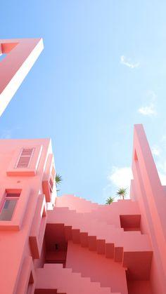 The pink exterior of a uniquely built building.