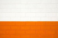 Brick wall painted white and orange, background full frame.