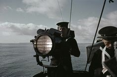 A signaller operates an Aldis lamp on board a British warship, 1942.