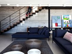 Rooftop Apartment with Exposed Concrete Walls exposed concrete walls living room decor #stairs #staircase #living room #concrete #interior