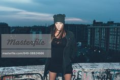Portrait of young woman in knit hat on roof terrace above city at night - Stock Photos : Masterfile