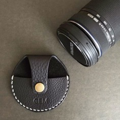 Leather Camera Cap Never lose your lens cap with this Leather Camera Cap! It attaches to your camera strap and stays in place. Made out of 100% Vegetable tanned leather and hand stitched with waxed thread. Comes with 100% cotton bag.