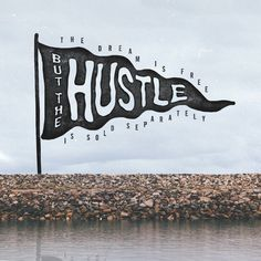 Dream is free, hustle sold separately, dream, hustle, free, separate, flag, blowing, waving, lake, lake shore, shore, rocks, water, hand let