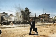 2004: Moises Saman. An Iraqi man walks by the scene of an attack on US Army Humvee that caused several American casualties in the Al-Waziriy #man #iraq #briefcase #old