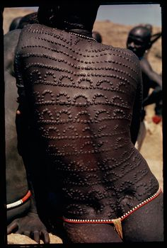 Welts, scars of beauty, pattern the entire back of a Nuba woman in Sudan, 1966.Photograph by Horst Luz, National Geographic Creative