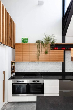 double-bowl sink, flat-panel cabinets, white cabinets, quartz benchtops, grey splashback, stainless steel appliances, concrete floors, with island, grey floor and black benchtop
