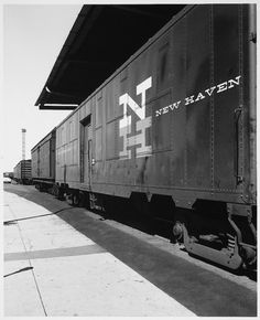 New Haven Railroad, NH Logo on Side, Parked train, Train on Diagonal into Distance at Rail Yard Over Hang, Cement and Paving next to Tracks #new #haven #herbert #matter