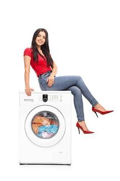 Beautiful woman sitting on a washing machine