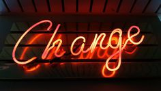 """A glowing red """"change"""" neon on a wall"""