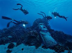 Picture of divers exploring a reef with fake moai off of Easter Island