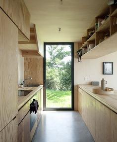 Beach Cottage Covered by a Dark Wood Cladding - InteriorZine