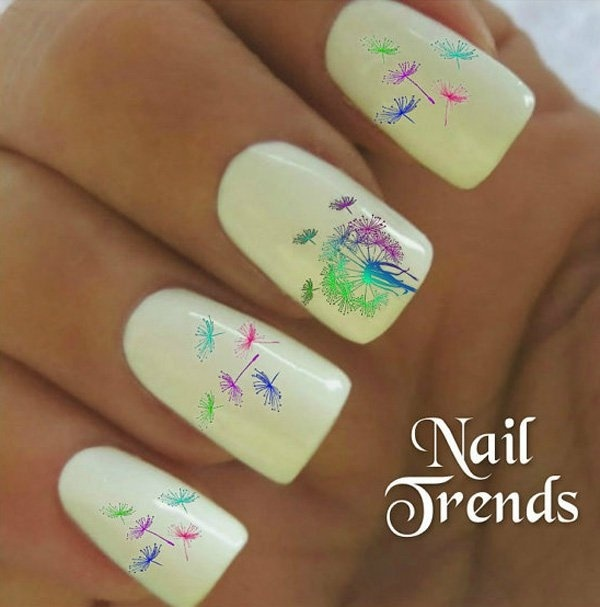 Start off with a white base color for this creative and multi colored Dandelion nail art. The Dandelions are painted in gradient and fading