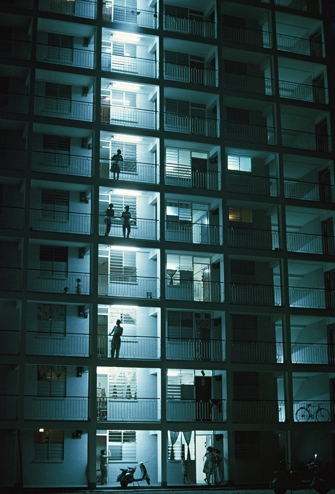 People stand on their balconies in the night air, Singapore, 2001 #urban #apartments #skyrise #home #balcony #photography #building #architecture #singapore