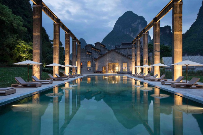Outdoor, Large Pools, Tubs, Shower, Landscape Lighting, Large Patio, Porch, Deck, Back Yard, Trees, and Grass An old sugarcane dock was turned into a swimming pool, which offers views of the Karst mountains and Li River from a distance.