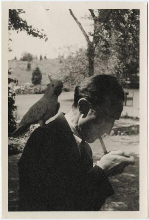Marcel Duchamp lighting a cigarette with a bird on his shoulder #photography #people