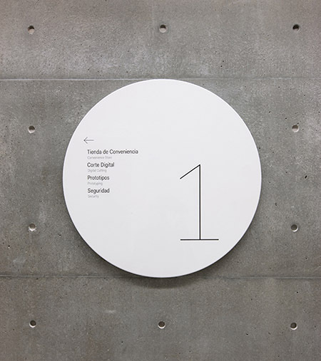 Identification and wayfinding signage appears on shiny metal discs that stand in contrast to the building's textured concrete walls. #textured #concrete #stand #identification #wayfinding #discs #appears #contrast #signage #metal #shiny #walls #buildings