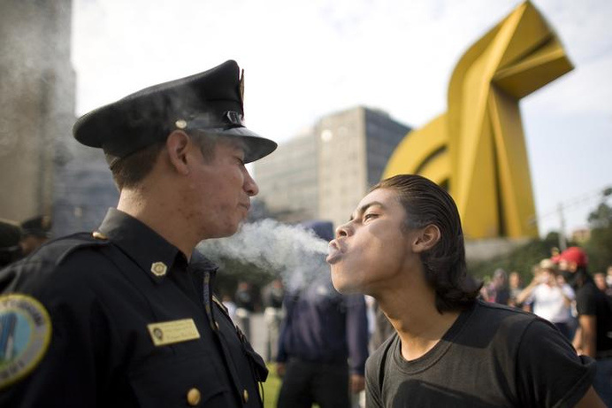 A protester blows marijuana smoke against the face of a police officer during a march to mark the 1968 Tlatelolco plaza massacre in Mexico C #protest #smoke #police #city #mexico #1968 #photography