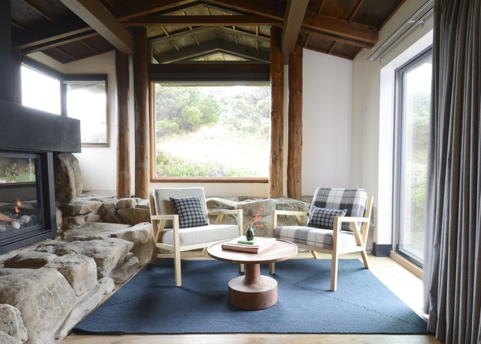 Ocean view suites have their own living rooms. Here, oak wood chairs upholstered in wool (one gray, one plaid) frame a midcentury-inspired coffee table.
