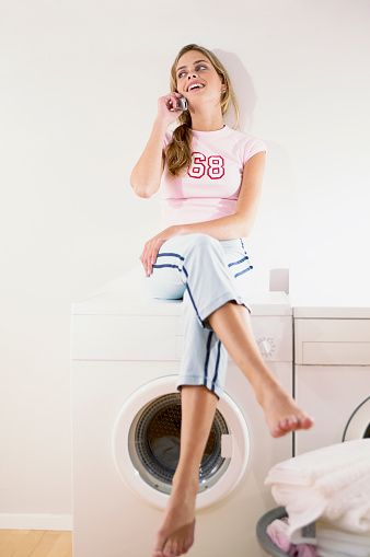 Woman sitting on clothes dryer