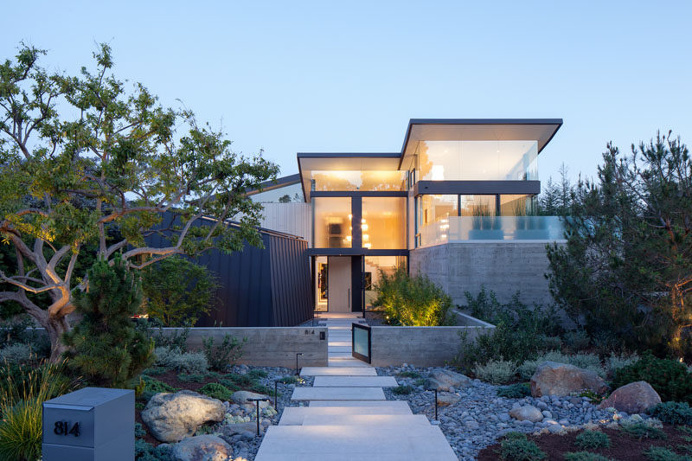 The front of this modern house has a path surrounded by landscaping, that leads to the large, light wood, pivoting front door. #architecture