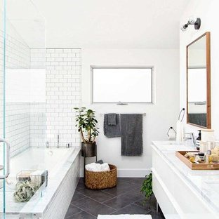 Danish white tile and subway tile slate floor and gray floor bathroom photo in Miami with flat-panel cabinets, white cabinets, white walls, an undermount sink, marble countertops and a hinged shower door